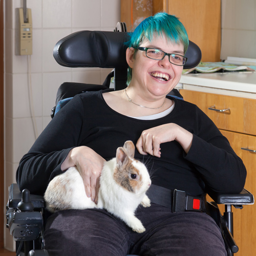 smiling lady in wheelchair with a bunny